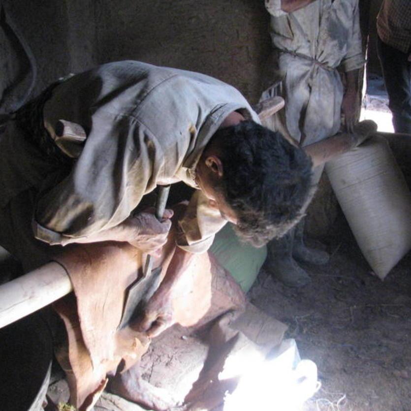 Das natürlich gegerbte Ziegenleder wird nochmal abgeschabt, um es dünner und weicher zu machen, Handarbeit in Afghanistan